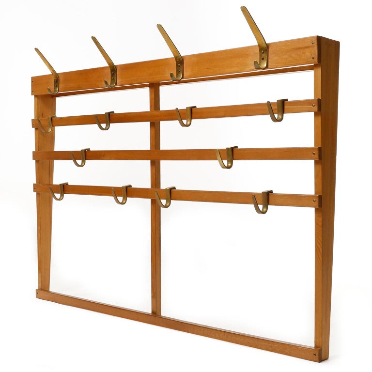 A large wooden coat check with patinated brass hooks manufactured in midcentury, circa 1950. It consists of a frame made of wood and six polished solid brass hooks with lovely patina. Five horizontal slats are mounted with patinated brass screws