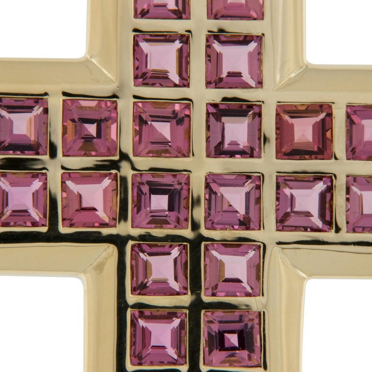 This classic shaped cross with a contemporary feel is stunning in 18 karat yellow gold. Accented with 5.28 Cttw. of square cut pink tourmalines which compliment the hue of the gold perfectly. Tourmalines are  considered a physical bridge to the