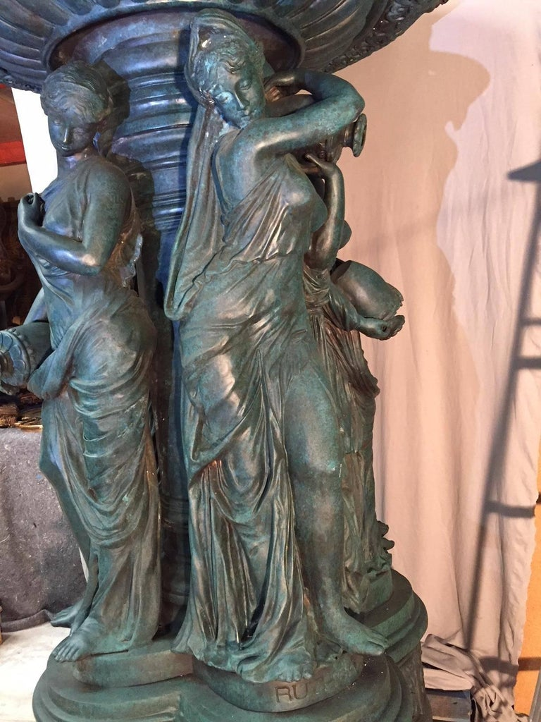 Magnificent patinated bronze garden fountain. The upper tier with four lifesize lion's heads over a 4 1/2 foot large basin supported by four neoclassical Maidens on stepped quatrefoil plinth inscribed