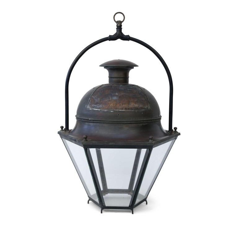 Large copper and brass hexagonal lantern with heavy iron handle and glass paneled sides. Copper patch in top on one side where hole had previously been cut. Can be wired for electricity for an additional cost.