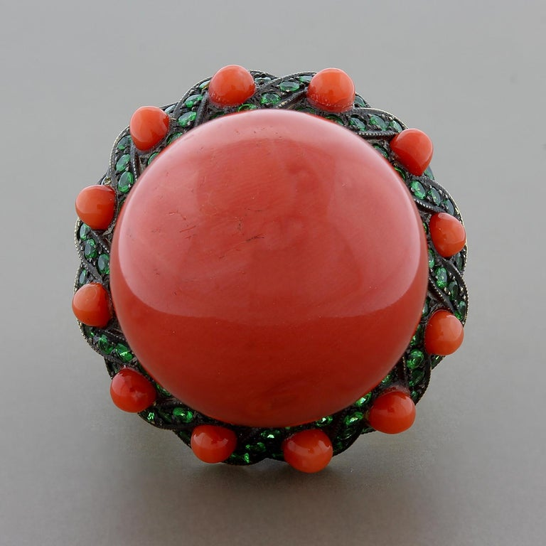 Straight from the reefs! Indulge in this extremely rare 21.3mm piece of coral, perfectly round. The massive coral bead is accented by bright green tsavorite and smaller coral beads, set in 18K yellow gold with a black rhodium finish giving the piece