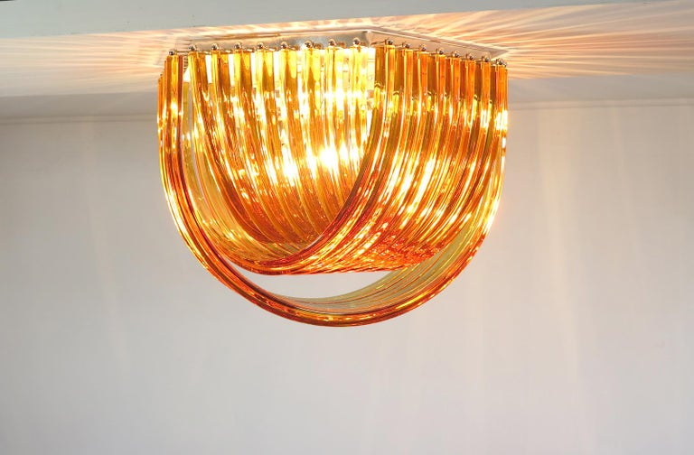 """Murano ceiling light amber glass with three layers of curving """"triedri"""" glass prisms on an exagonal chrome structure. A dynamic form, changing as you move around it, due to the overlapping levels of amber glass with light shining through. Period:"""
