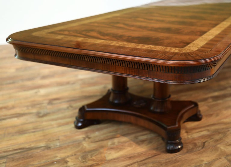 This is made-to-order large mahogany dining table made in the Leighton Hall shop. This is one of our flagship tables and is known as the King Demure dining table. It has a transitional design inspired by the original 18th century Regency style