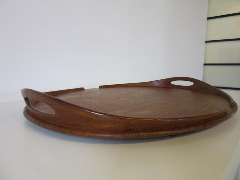 A very large and wonderful teak wood tray with sculptural handles and edge trim, the bottom has runners and is branded Dansk Denmark with the four ducks mark making this a early piece from the manufacturer.