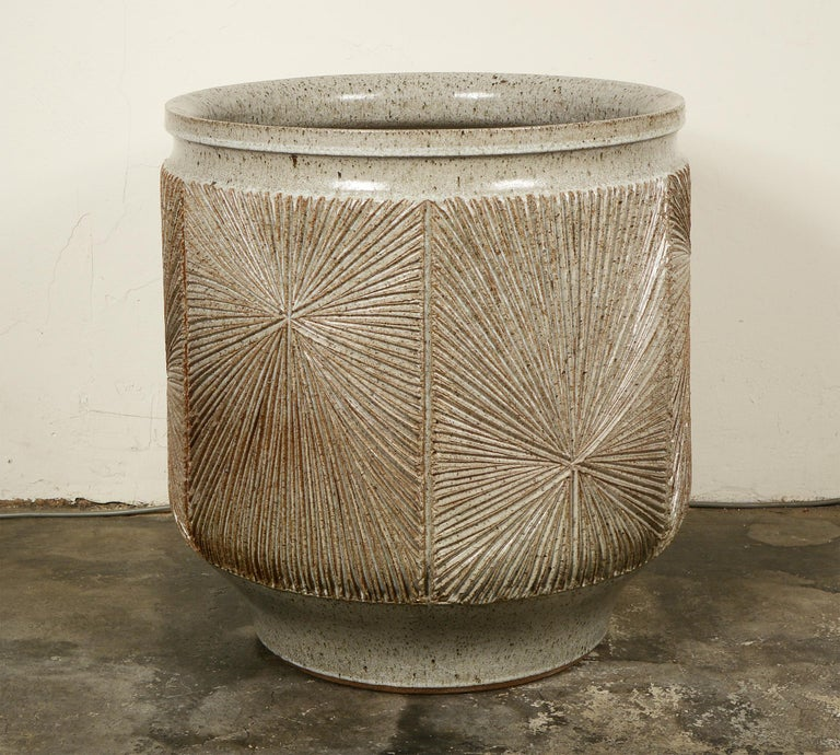 Glazed stoneware planter by David Cressey and Robert Maxwell for their company Earthgender Ceramics. This has a speckled light gray glaze with the stoneware showing through on the high spots. The planter is not drilled. This has spent all its time