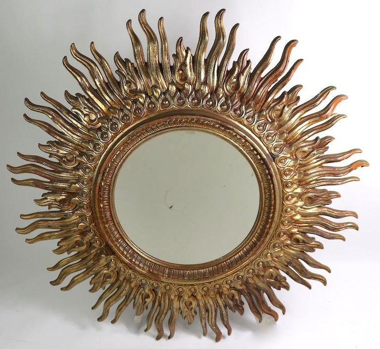 Large circular sunburst frame mirror with cast resin faux gilt frame. The frame has radiating rays surrounding the circular glass mirror. This item is in very good original condition, the center mirror has a minor dark spot, which is