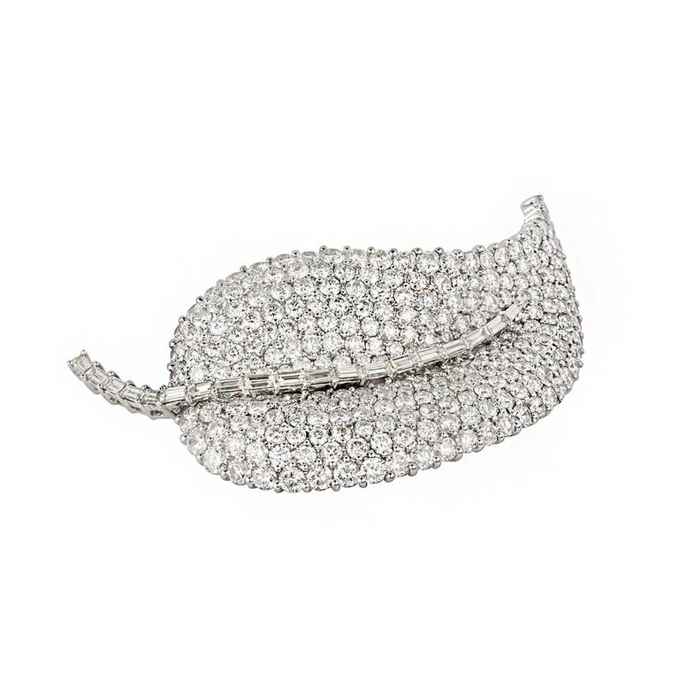 An 18k white gold diamond set leaf brooch. The body of the brooch is composed of round brilliant cut diamonds, each individually claw set, accentuated by the stem composed of claw set baguette cut diamonds. The diamonds total approximately