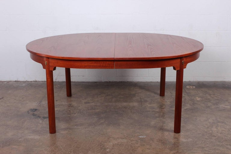 A large teak dining table with brass details. The table measures 66.75