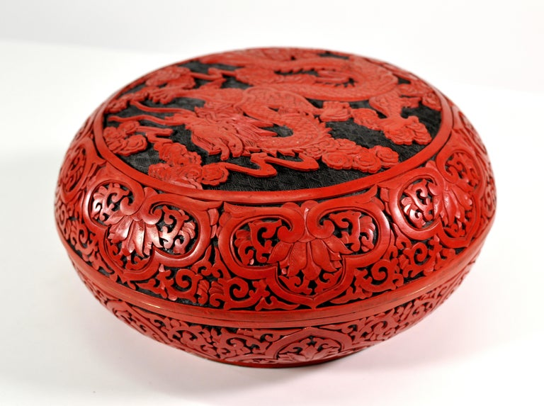 A large vintage Chinese red cinnabar box with deep relief carved lid depicting flowers, leaves and a dragon. The round box has a domed lid and a black lacquer interior.