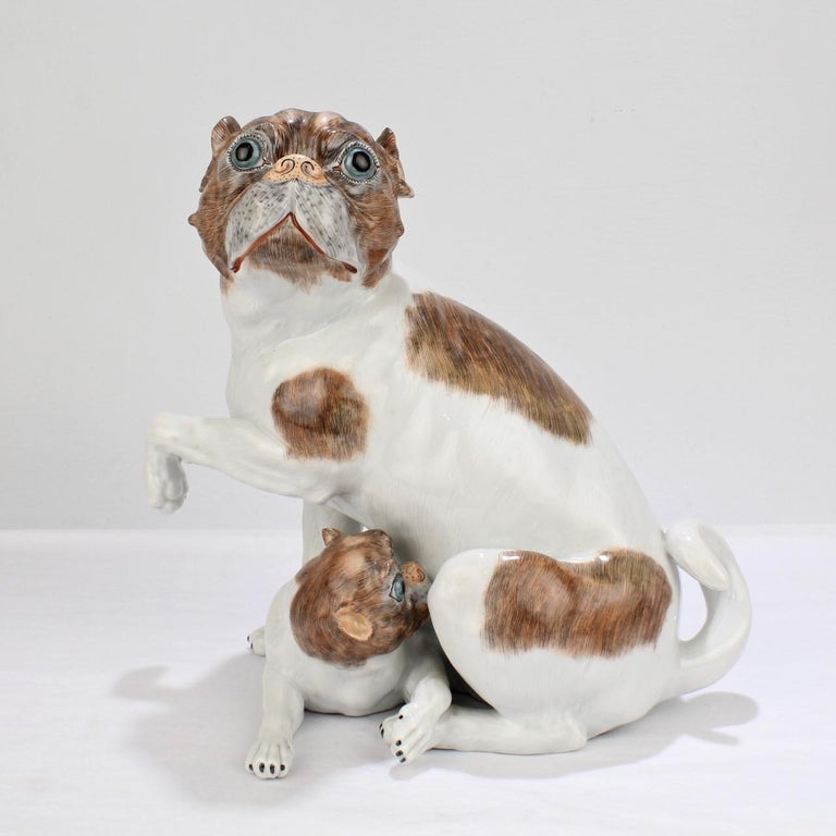 A wonderful Dresden porcelain figurine of a mother pug and her puppy.  The figurine is modeled after the 18th century Meissen figurine by Johannes Kaendler with the puppy nestled snugly under the mother's belly.   Each dog is decorated in brown