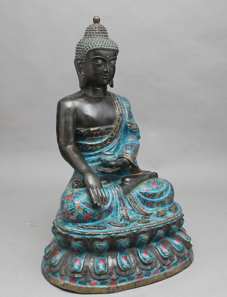 A large early 19th century bronze and cloisonne Buddha of superb quality, the seated Buddha with cloisonne enamel for the garment, with one hand holding a small cup / bowl, seated upon lotus flowers, circa 1820.