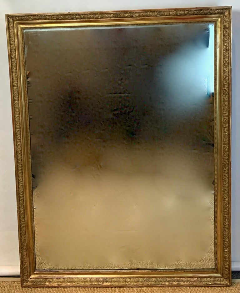 An early 19th century neoclassical French elegantly carved giltwood mirror of particularly large scale with original glass and wood back.