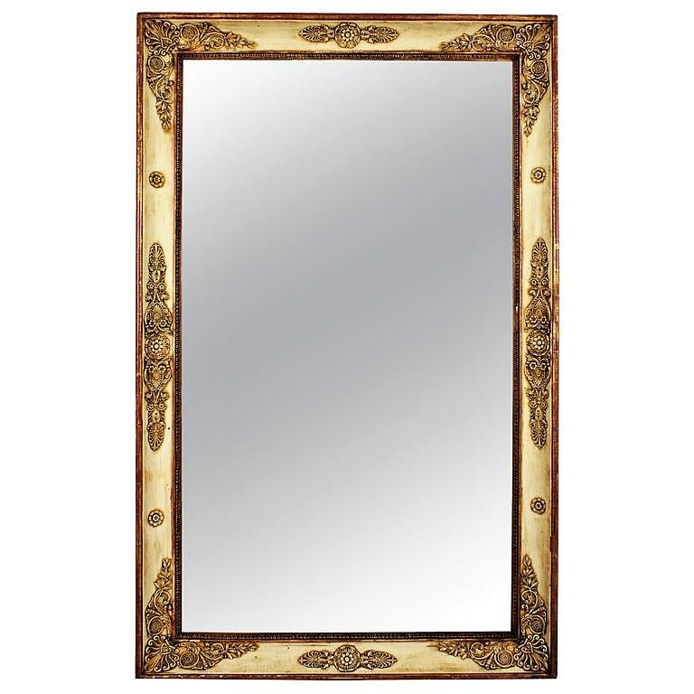 Beautiful Empire period large rectangular mirror with neoclassical relief ornamentation with gilded details and a very nice patina in beige color with red accents, France, circa 1810. It wears its original antique glass that shows a terrific aged