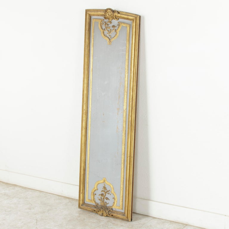 Standing at an impressive 73 inches in height, this large asymmetrical architectural panel from the early 19th century was originally part of the boiseries or paneling in a French manor house. Painted in a Marie Antoinette grey and surrounded by a