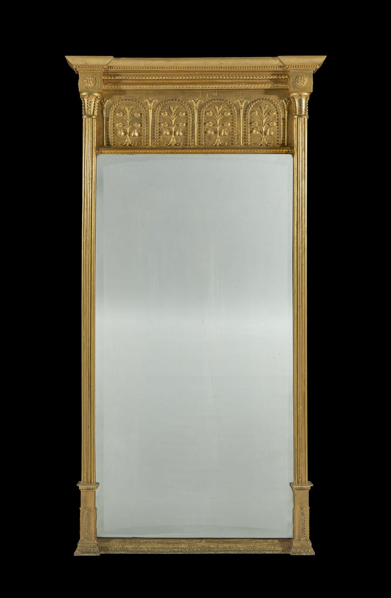 The breakfront cornice is decorated with beaded mouldings and sits on a frieze that is populated with stylized flowers and beaded arches above the original bevelled glass plate. The pier mirror is flanked with reeded pilasters, block capitals and