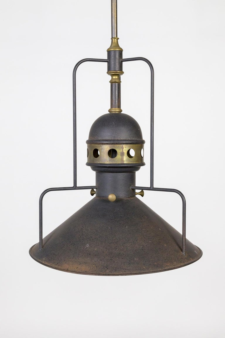 A large, unique, mixed metal light in dark bonze color with brass accents. The cogs were used to move the light along the work line and to raise and lower it. A striking example of industrial craftsmanship. American, circa 1905. Measures: 17.75
