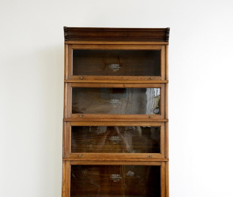 Large early 20th century bookcase by Soennecken  - Solid oak with glass windows - Each window lifts up and slots in - Each section is branded with gold lettering and flower detailing - Brass flower handles - Comes apart in 8 sections - Made