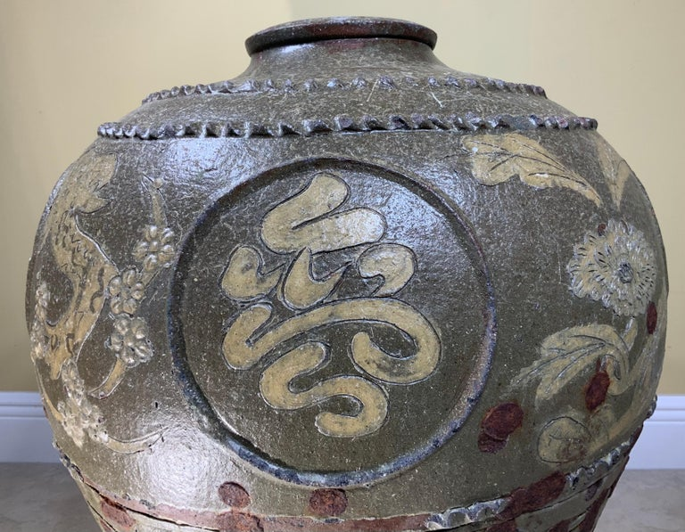 This jar made by hand with exceptional floral and Chinese calligraphy motifs marked on it, and beautifully glazed with olive color. The unique look in this jar show as that while in the process of making the jar, the artist add some pieces of metal