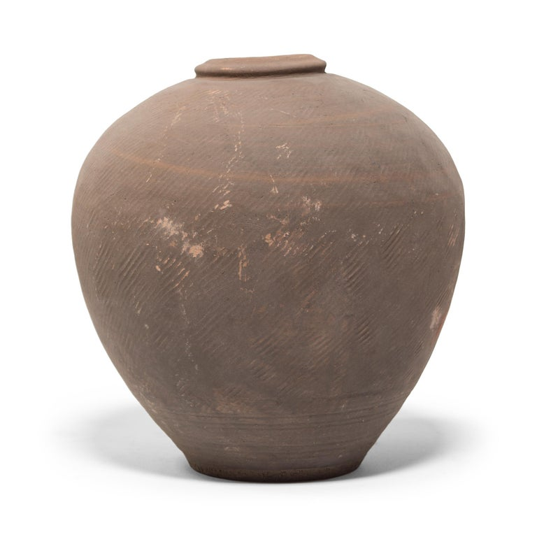 This 19th century ceramic jar from northern China is formed in a traditional shape meant for storing wine and spirits made from rice and grains. Variation during firing has resulted in delightfully irregular patterns over its textured surface, and