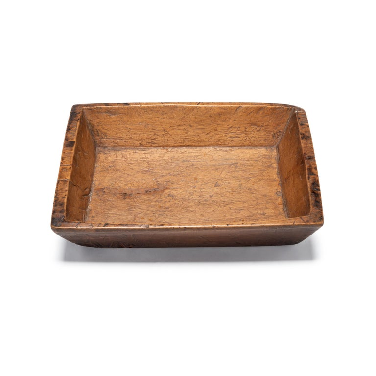 Carved from pine, this hundred-year-old tray made in northern China charms with its rustic character and simple shape. Marked with use and distinguished by the natural grain and knots of wood, the tray brings its timeless appeal to modern interiors