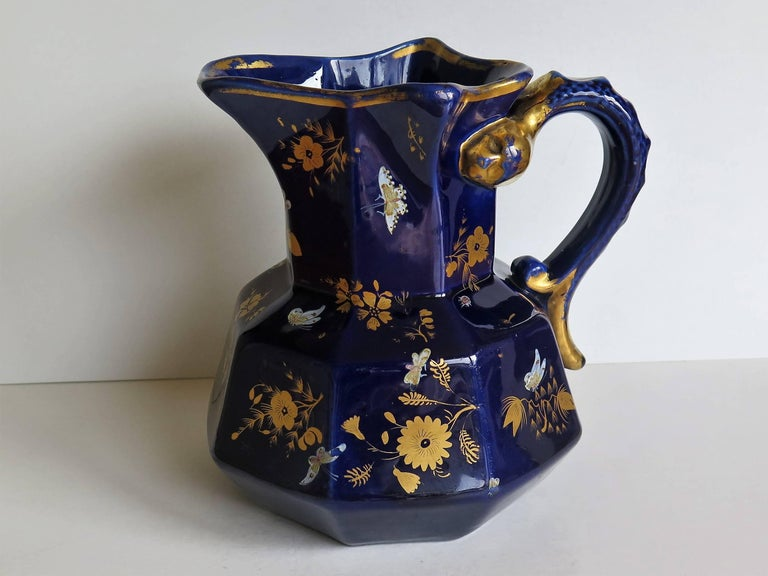 This is a large ironstone jug or pitcher in the Hydra Shape with a rare pattern, made by Mason's, of Lane Delph, Staffordshire, England, Circa 1825.   The jug is octagonal with a good snake loop handle.  The piece is richly hand-decorated in gold