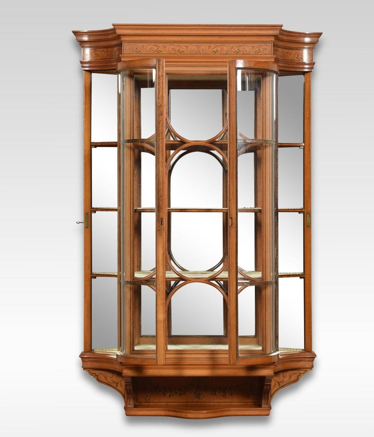 Edwardian painted satinwood wall hanging display cabinet, the stepped cornice above a foliate painted frieze and ribbed glass panel flanked by two unusual concave doors enclosing three shelves over a short, recessed, shelf and foliate swag painted