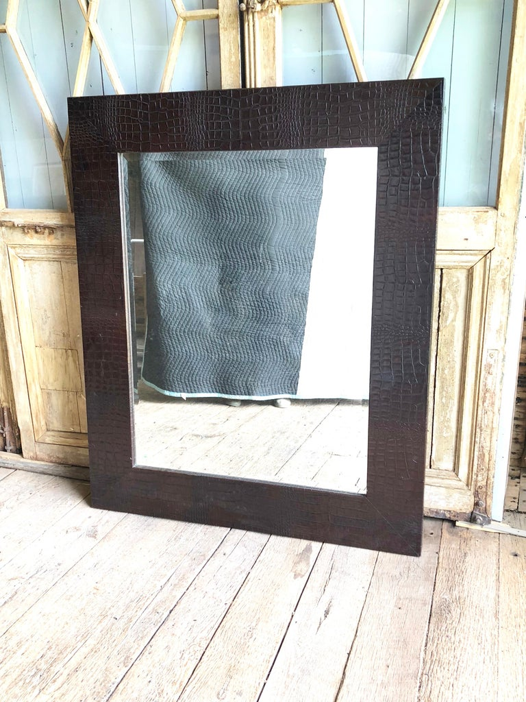A large wall mirror with heavy beveled-glass plate in a faux alligator embossed leather frame.