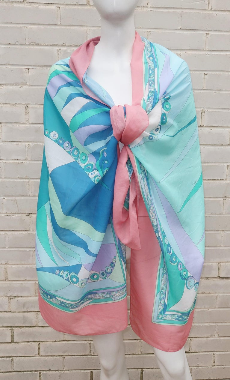 Perfect for warmer weather and sultry days at the beach! This fine muslin cotton Emilio Pucci scarf is both long and lightweight enough to wrap and drape to your heart's content. It is a classic mod psychedelic print in shades of salmon pink, aqua,