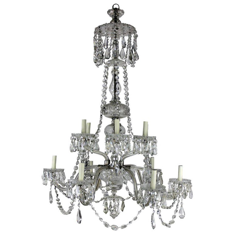A large English cut-glass chandelier of good quality. Of six down-swept and six up-swept arms, decorated heavily with swags and pendant drops.