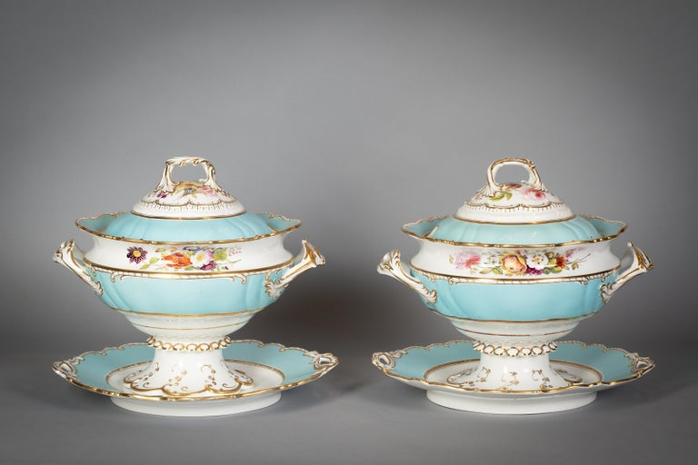 With a soft turquoise ground, painted with a fine spray of flowers, with gilt scroll and dash borders. Comprising pair of covered tureens and stands, pair of vegetable tureens, well and tree platter, 9 soup plates, 57 dinner plates, 3 platters.