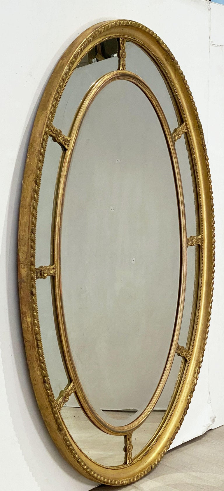 A handsome large English segmented gilt oval wall mirror in the Adam style, featuring a gilt wood oval segmented marginal border mirror.  The carved, rope-edged frame showing eight small inner mirrors with eight leaf and flower head divides,