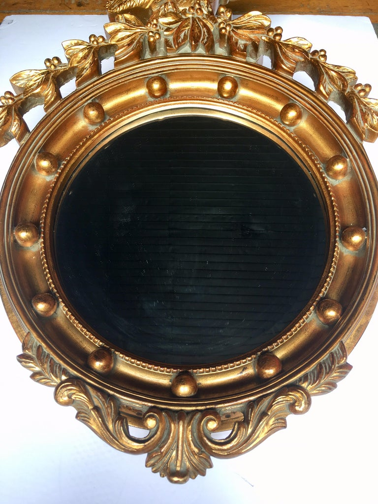 Large dimensional traditional Federal style round mirror with perched eagle flanked by acanthus surmounting. Carved-like frame is constructed of a light weight composition and is finished in a metallic gold painted finish. Beveled mirror measures 16
