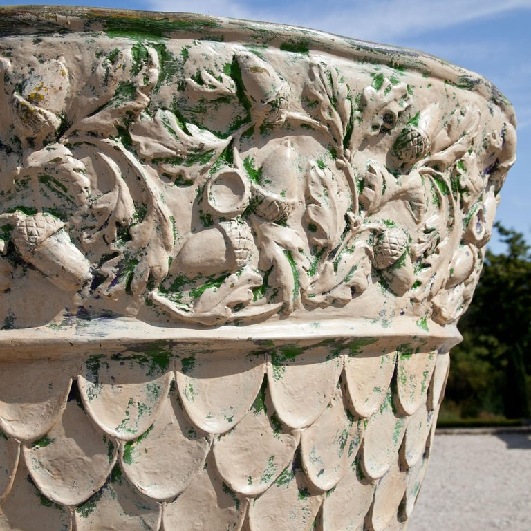 Large fiberglass planter standing on a square plinth. The planter is decorated with vines and scales and shows traces of an old paint.
