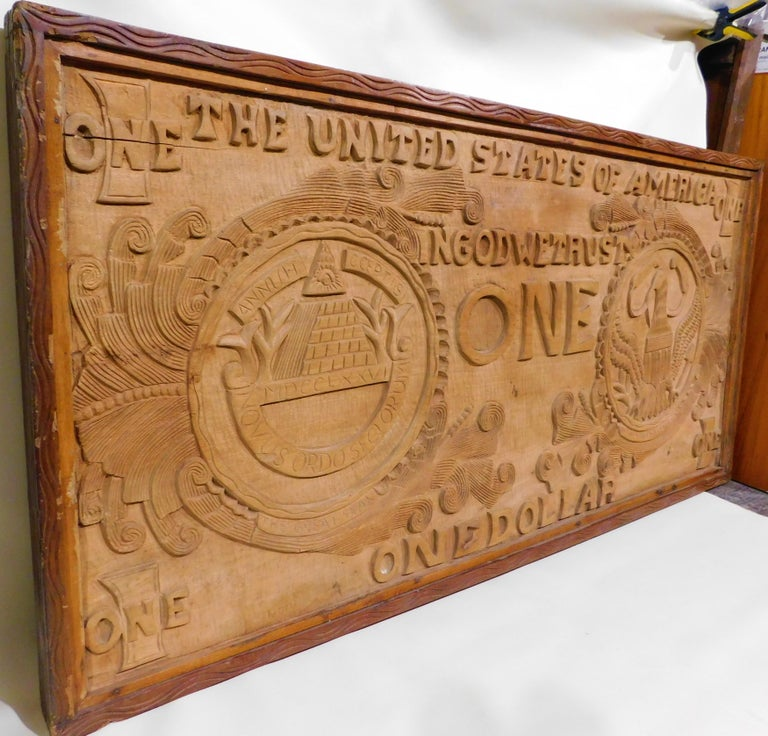 Over four feet long and two feet wide this hand carved U.S.A. dollar bill can be just hung on the wall or there are evidence on the back where legs where or could be attached to make a coffee table out of it. A neat Folk Art piece. Initials GM