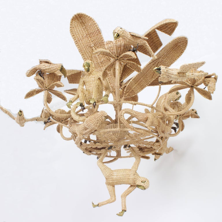 Folky Mario Lopez Torres six-light jungle chandelier constructed of an iron frame wrapped with wicker or reed. Featuring monkeys, parrots, panthers and alligators having a party under the palm leaves.