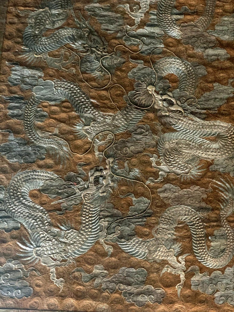 An impressive Japanese embroidery tapestry circa 1890s Meiji period, presented with brocade border on linen canvas in a Lucite shadow box. The stunning design features three dragons coiling and flying in the clouds. The high relief technique used to