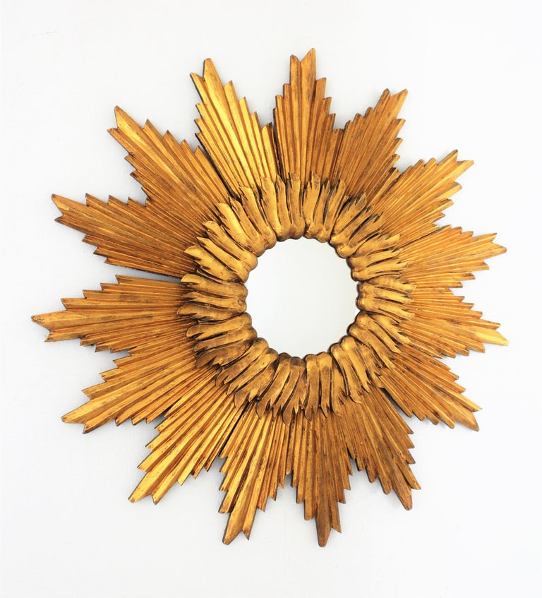 A magnificent carved wood double layered sunburst mirror with gold leaf finish and convex glass. The glass is framed by a circular layer of short beams and a large layer with giltwood beams with sunburst or starburst disposition. Glass diameter:
