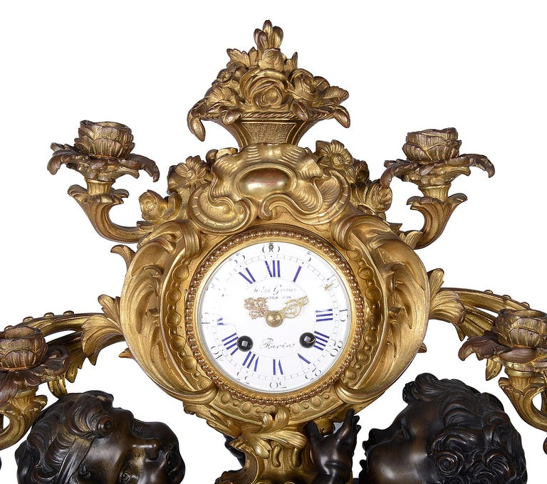 A very impressive 19th century French gilded ormolu and bronze mantel clock, having a pair of bronze putti entwined around the eight day duration chiming clock with four scrolling foliate candelabra and raised on a Rococo style base.
