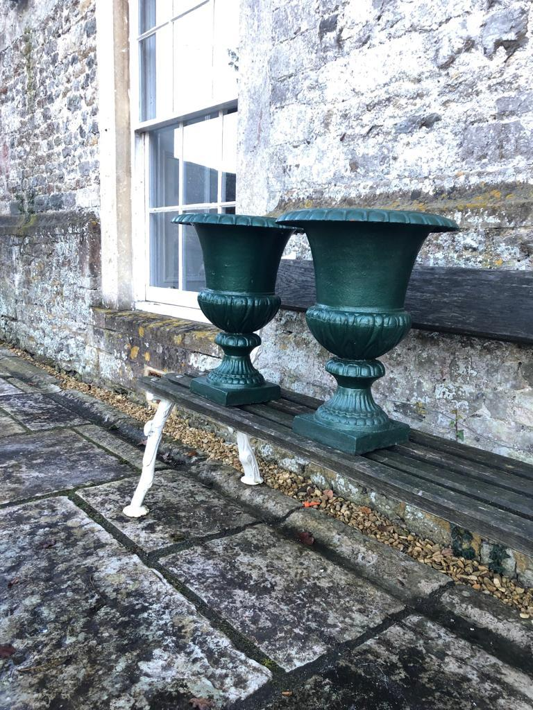 This is a gorgeous and early English cast iron campana urn with a plain, everted rim and semi-lobed body. In old green paint, it would make a real statement beside your front door potted up with a profuse arrangement of annuals or wavy grasses. It