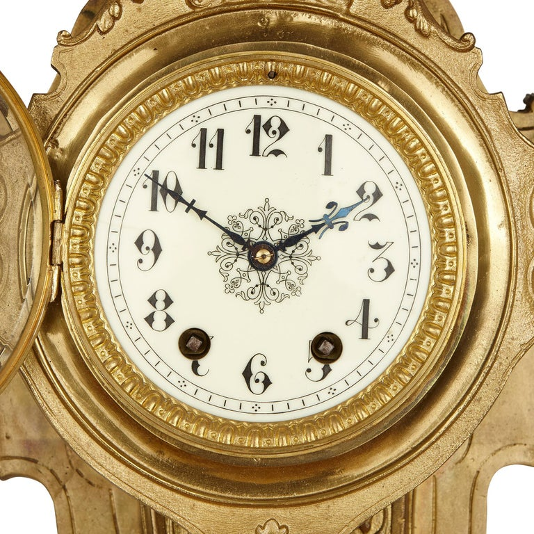 This large, gilt bronze wall clock is a magnificent and highly unusual piece. At the centre of the design is a circular enamel dial, with Arabic Numerals, which is set within a gilt bronze case, with a lion's head at its top, and shield contained