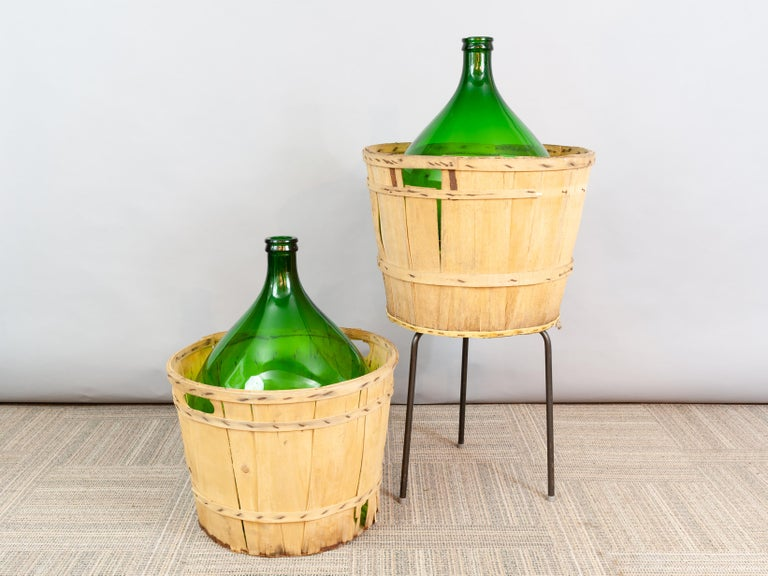 Large French antique emerald green demi-john in its original wooden carrying basket. The bottle can be used for decorative purposes only or for the storing of wine or perhaps olives. They make a wonderful centre-pieces for a large table display,