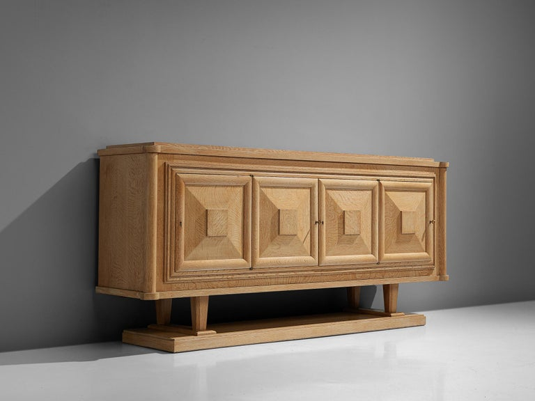 Sideboard, oak, France 1930s.  Large credenza in oak. The sideboard has four doors, all with beautifully designed wooden graphical patterns. The diagonal lines with added squares and a frame emphasize the three-dimensional character of the front.