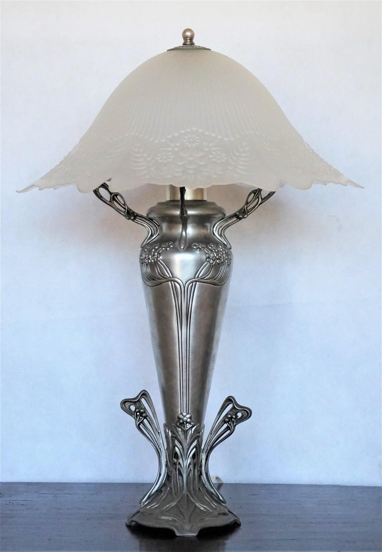 A large Art Deco handcrafted pewter vase shape table lamp with beautiful high relief glass shade, France 1930s. One E27 light bulb socket. Measures: Height 25 in (63.5 cm) Diameter 16 (40.5 cm).