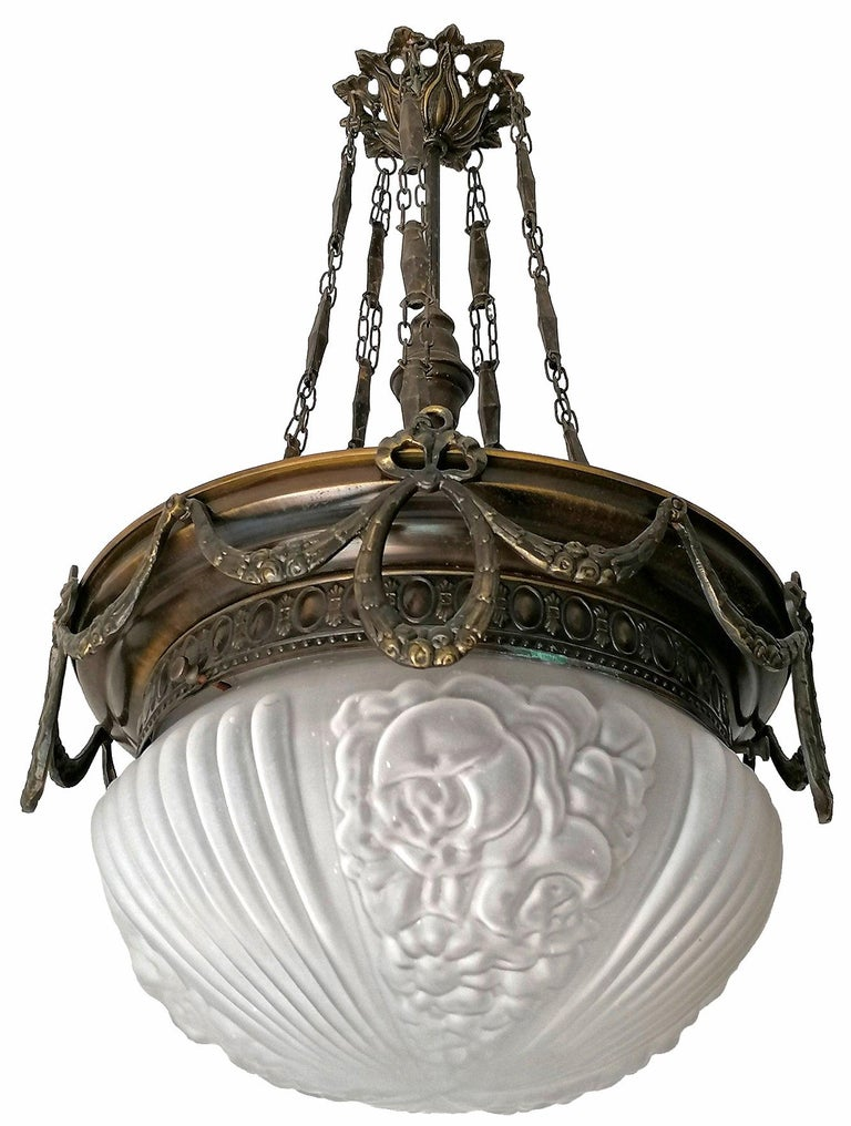 A wonderful ceiling fixture decorated with fine ornaments and garlands. In very good condition, original frosted high relief glass dome without damages, brass with beautiful patina, France, early 20th century.  Dimensions: Height 27.56 in. (70