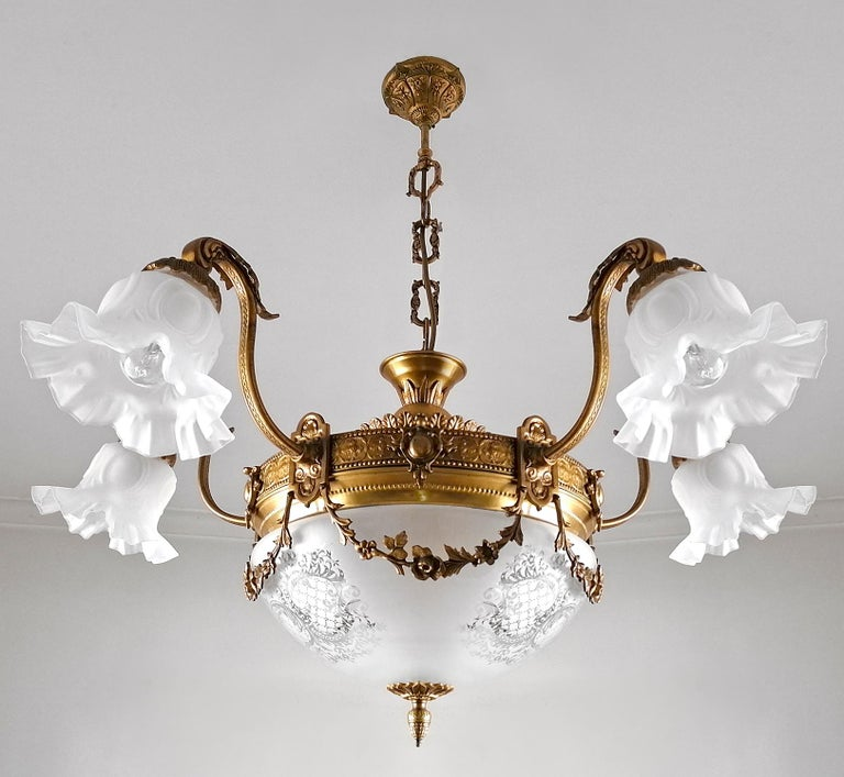 A wonderful gilt bronze and etched-glass 8-light ceiling fixture decorated with fine ornaments and garlands, France, early 20th century. Dimensions Height: 31.5 in. (80 cm) Diameter: 35.44 in. (chain 10 in.)/(90 cm/chain 25cm) 8 light bulbs