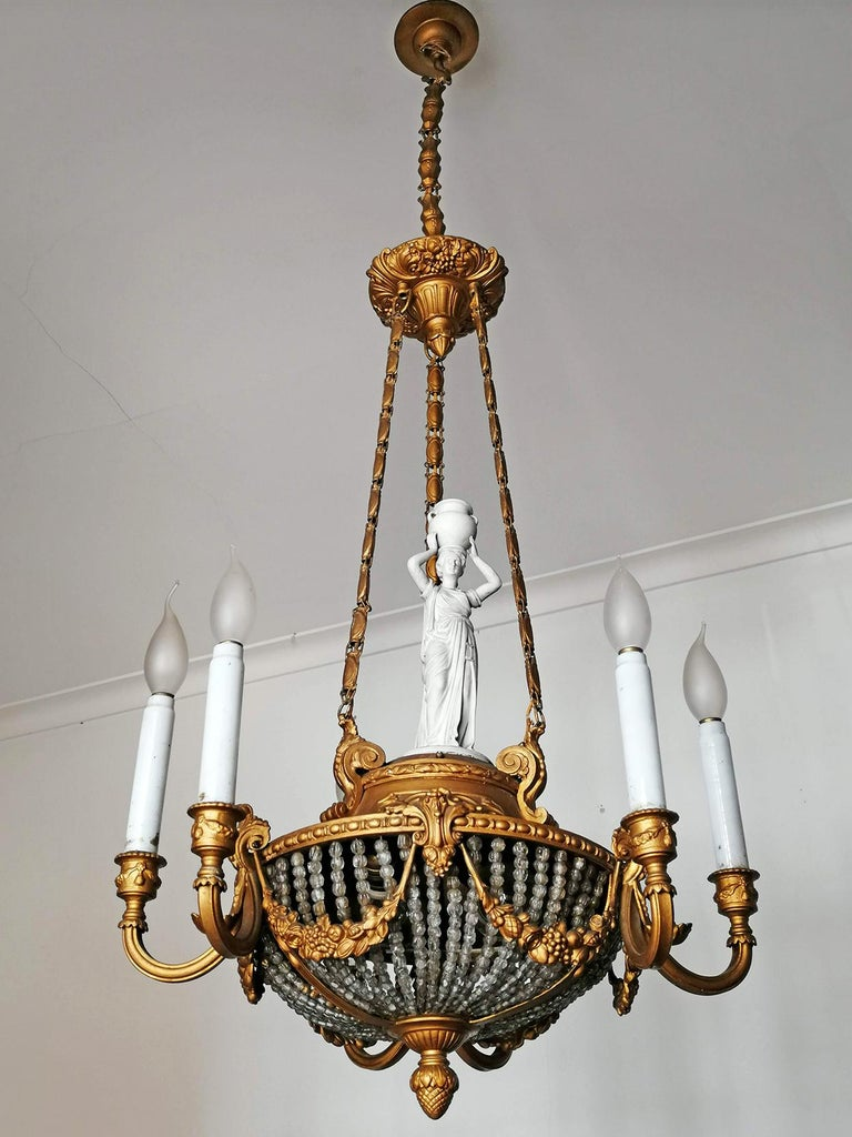 A wonderful gilt bronze and beaded-glass 8-light ceiling fixture decorated with fine ornaments and garlands, France, late 19th century. Porcelain Caryatid and white glass candles. Measures: Diameter 21.7 in/ 55 cm Height 53.2 in (chain 15.8 in)/