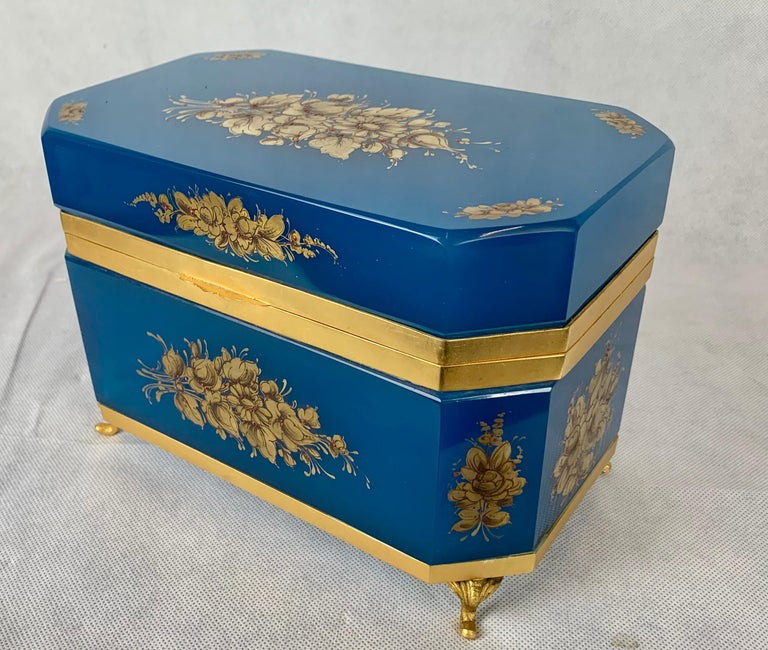Large French blue Opaline glass box.  Hand painted with gilt floral sprays. Hinged bronze doré frame with thumb catch and cabriole feet. The rectangular shape has cut corners and gilt decoration on all sides. The opaline box is in beautiful