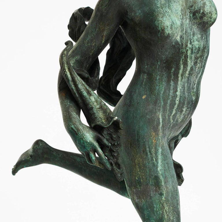 A near full size French Verdigris patinated bronze nymph, frolicking on one leg with ribbon and flowers, holding a couch shell.