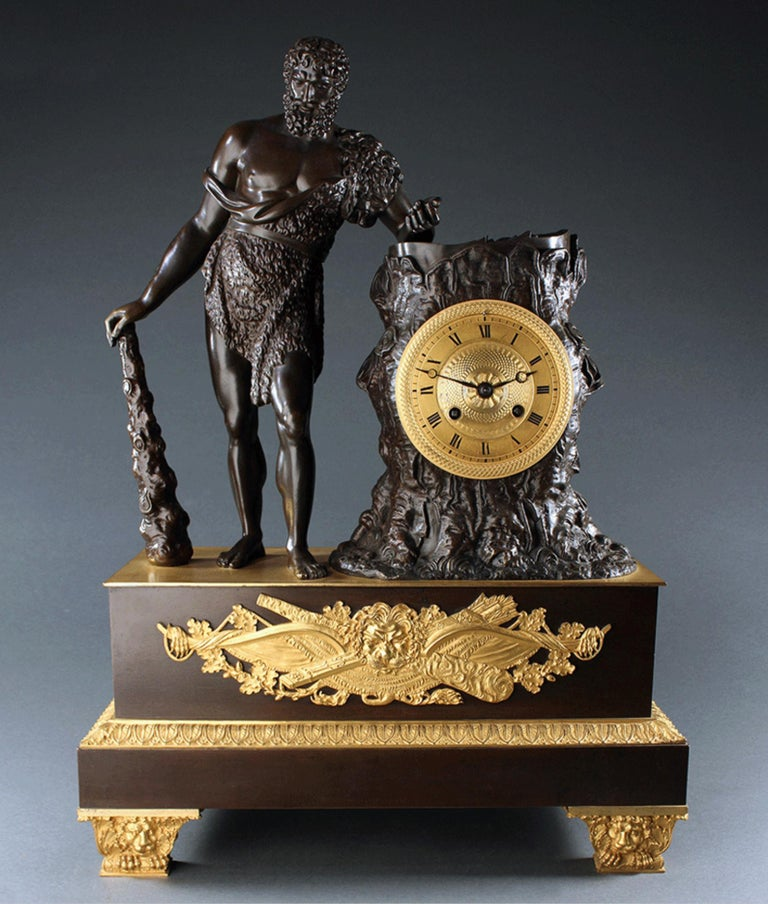 Classic early 19th century French Empire ormolu gilt and patinated bronze mantel clock depicting one of the twelve labours of Hercules/Herakles, stealing the apple of Hesperides. Beautifully cast and chased this large size clock is surmounted by a