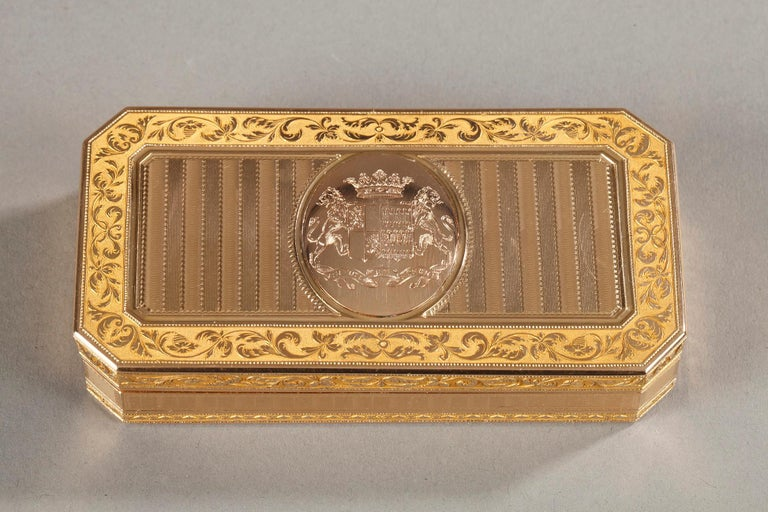 Large rectangular snuffbox with angled corners sides. The hinged lid is embellished with a guilloche pattern with alternating parallel and horizontal strips of matt and shiny gold. In the center of the lid a medallion presents the coat of arms of an